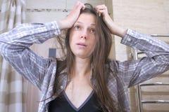 La mujer soñolienta a quien haber despertado con una resaca en el intento del cuarto de baño se pone en orden foto de archivo libre de regalías