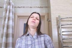 La mujer soñolienta a quien haber despertado con una resaca en el intento del cuarto de baño se pone en orden foto de archivo