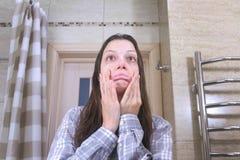 La mujer soñolienta a quien haber despertado con una resaca en el intento del cuarto de baño se pone en orden fotos de archivo