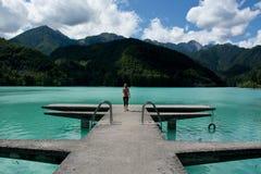 La mujer sola en el embarcadero en un día del verano tardío en el lago fotografía de archivo