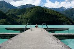 La mujer sola en el embarcadero en un día del verano tardío en el lago fotos de archivo libres de regalías