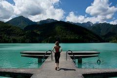 La mujer sola en el embarcadero en un día del verano tardío en el lago imágenes de archivo libres de regalías