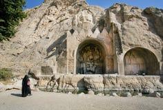 La mujer sola en musulmanes viste el hijab que se coloca cerca del monumento Taq-e Bostan Imágenes de archivo libres de regalías