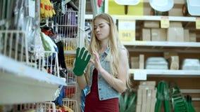 La mujer sola está poniendo de guantes protectores del estante en una tienda del hogar metrajes