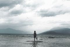 La mujer sola mira infinito y la naturaleza incontaminada en un día tempestuoso Imagen de archivo