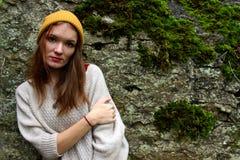 La mujer sonríe en un suéter y un sombrero con un pompón imagenes de archivo