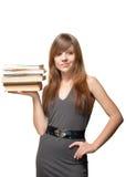 La mujer sonríe y sostiene una pila de libros Imágenes de archivo libres de regalías