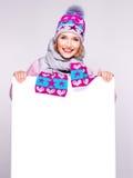 La mujer sonriente adulta en sombrero del invierno sostiene la bandera blanca Foto de archivo libre de regalías