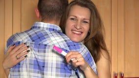 La mujer sonriente alegre de la esposa abraza a su hombre del marido con la prueba de embarazo a disposición almacen de video