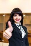 La mujer sonriente atractiva en la oficina que mira la cámara manosea con los dedos para arriba Fotografía de archivo