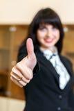 La mujer sonriente atractiva en oficina muestra el pulgar para arriba Imagenes de archivo