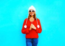 La mujer sonriente bonita con la piruleta en rojo hizo punto el suéter Fotografía de archivo
