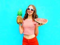La mujer sonriente bonita de la moda está llevando a cabo una piña y una rebanada de sandía Foto de archivo