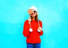 La mujer sonriente bonita del retrato cierra la cara con la piruleta en suéter hecho punto rojo Fotos de archivo