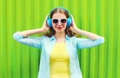 La mujer sonriente bonita feliz escucha la música en auriculares sobre verde Fotografía de archivo libre de regalías