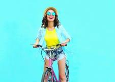 La mujer sonriente bonita feliz monta una bicicleta sobre azul colorido Foto de archivo