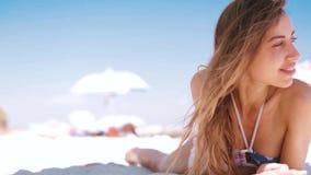 La mujer sonriente bronceada hermosa est? mintiendo en la playa en una arena blanca, relaj?ndose y escucha m?sica del tel?fono co almacen de video