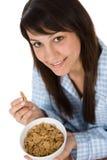 La mujer sonriente come el cereal sano para el desayuno Fotos de archivo libres de regalías
