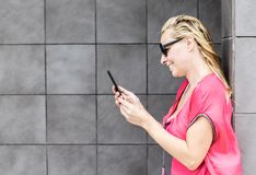 La mujer sonriente comprueba el teléfono móvil Imágenes de archivo libres de regalías