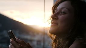 La mujer sonriente con aplicaciones de pelo rizado llama por teléfono en una puesta del sol, se sostiene en manos en ciudad metrajes