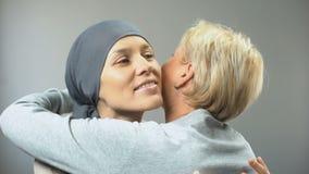 La mujer sonriente con el cáncer que abraza a su amigo femenino, espera la curación, ayuda almacen de video