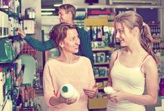 La mujer sonriente con el cuerpo del embalaje del adolescente de la muchacha cuida mercancías Fotografía de archivo libre de regalías