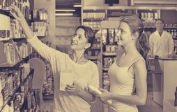 La mujer sonriente con el cuerpo del embalaje del adolescente de la muchacha cuida mercancías Fotografía de archivo