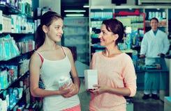 La mujer sonriente con el cuerpo del embalaje del adolescente de la muchacha cuida mercancías Fotos de archivo
