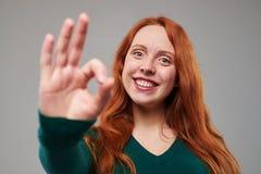 La mujer sonriente con el donante rojo del pelo los pulgares sube gesto Fotografía de archivo