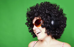 La mujer sonriente con el pelo afro escucha la música con los auriculares Foto de archivo