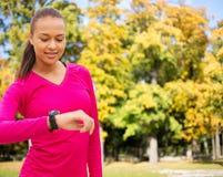 La mujer sonriente con el reloj del ritmo cardíaco en el otoño parquea Fotos de archivo