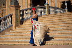 La mujer sonriente con el vestido azul del flamenco en Plaza de Espana imita el movimiento del ` s del torero imagen de archivo libre de regalías