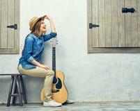 La mujer sonriente con la guitarra que se sienta en la calle bench Fotos de archivo libres de regalías
