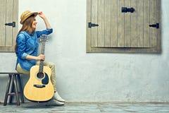 La mujer sonriente con la guitarra que se sienta en la calle bench Foto de archivo libre de regalías