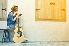 La mujer sonriente con la guitarra que se sienta en la calle bench Imagen de archivo libre de regalías