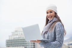 La mujer sonriente con invierno viste en usar su ordenador portátil Fotografía de archivo