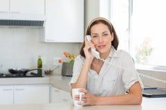 La mujer sonriente con la taza de café usando línea horizonte llama por teléfono en cocina Imagenes de archivo