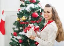 La mujer sonriente con las decoraciones de la Navidad acerca al árbol de navidad Imágenes de archivo libres de regalías