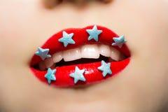 La mujer sonriente con los labios pintó las estrellas rojas del lápiz labial y del caramelo Imagen de archivo