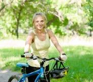 La mujer sonriente con una montaña monta en bicicleta en parque Fotografía de archivo