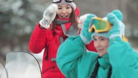 La mujer sonriente cuenta una historia divertida y lleva gafas del esquí en el bosque del invierno almacen de video