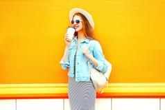 La mujer sonriente de la moda bebe un café en una naranja Foto de archivo
