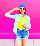 La mujer sonriente de la moda con una taza de café escucha la música en rosa Fotos de archivo