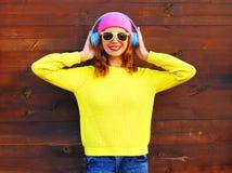 La mujer sonriente de la moda escucha la música en auriculares Foto de archivo libre de regalías