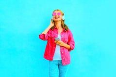 La mujer sonriente de la moda escucha la música en los auriculares inalámbricos Imagen de archivo