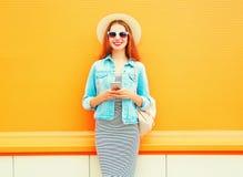 La mujer sonriente de la moda está utilizando el smartphone en la ciudad Fotos de archivo libres de regalías