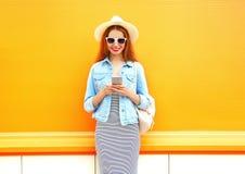 La mujer sonriente de la moda está utilizando el smartphone en la ciudad Imagen de archivo