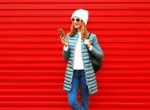 La mujer sonriente de la moda está utilizando smartphone Imagen de archivo