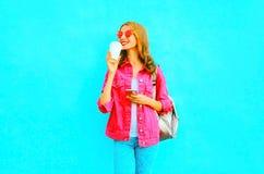 La mujer sonriente de la moda que usa smartphone en chaqueta rosada del dril de algodón sostiene la taza de café Foto de archivo