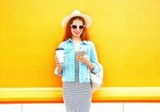 La mujer sonriente de la moda que usa un smartphone sostiene la taza de café Imágenes de archivo libres de regalías